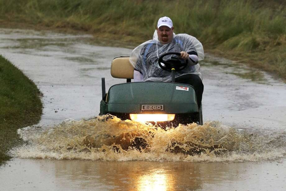 A golf cart makes it way through a flooded cart path as rain falls at Merion Golf  Club, in Ardmore, Pa., early Monday, June 10, 2013. The 2013 U.S. Open championship will be played at Merion, June 13-16. (AP Photo/Gene Puskar)