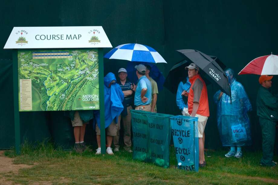 Spectators wait out a rain delay during the first round the US Open at Merion Golf Club June 13, 2013 in Ardmore, Pennsylvania. AFP PHOTO/Brendan SMIALOWSKIBRENDAN SMIALOWSKI/AFP/Getty Images