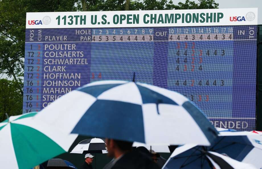 ARDMORE, PA - JUNE 13:  Patrons use umbrellas while play is suspended due to weather during Round One of the 113th U.S. Open at Merion Golf Club on June 13, 2013 in Ardmore, Pennsylvania.  (Photo by Scott Halleran/Getty Images)