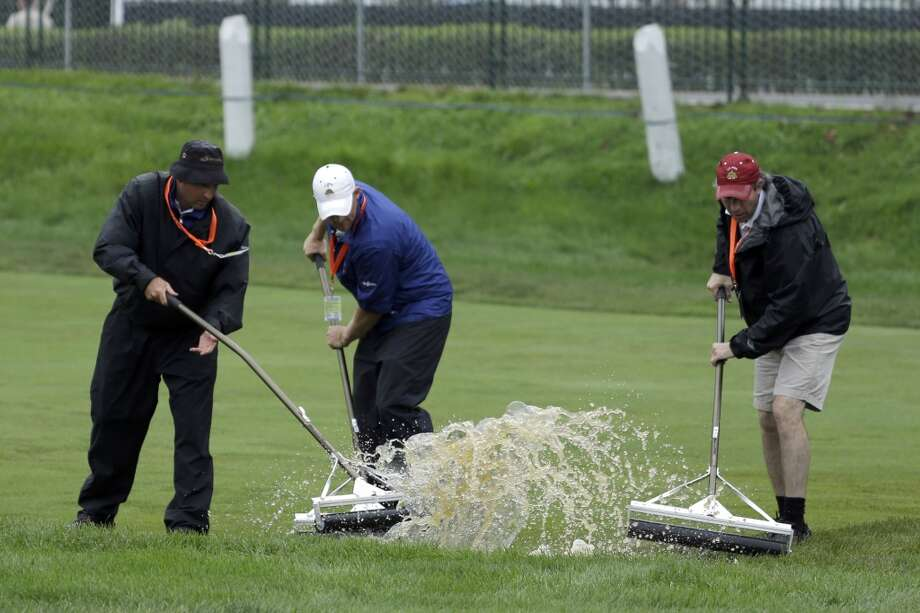 Course workers clear water from the second fairway after a weather delay during the first round of the U.S. Open golf tournament at Merion Golf Club, Thursday, June 13, 2013, in Ardmore, Pa. (AP Photo/Darron Cummings)