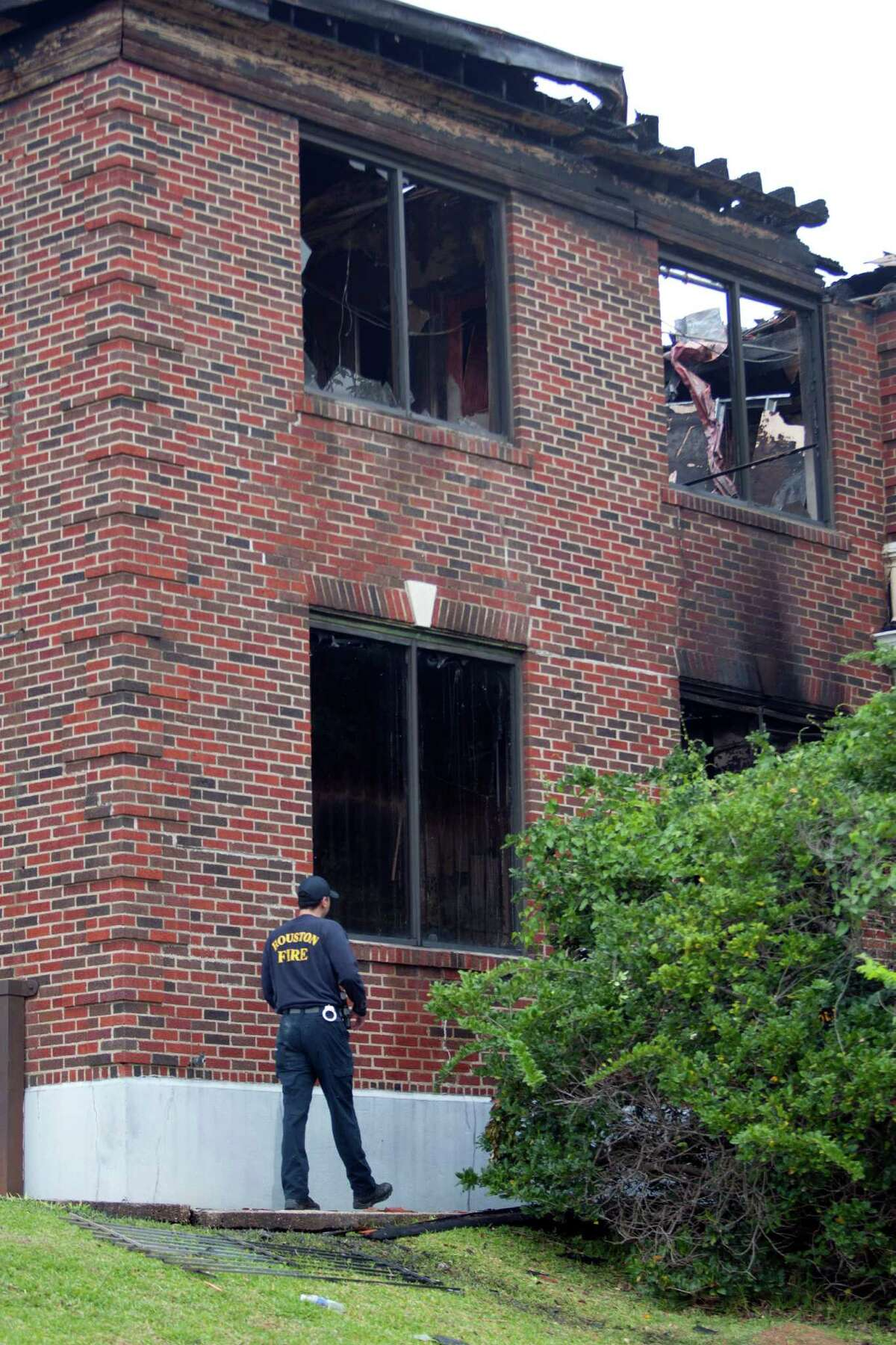 Arson investigators investigate a fire in part of the former Jefferson Davis Hospital after an early morning two-alarm fire gutted the building known to many as one of the most haunted buildings Thursday, April 25, 2013, in Houston. The blaze broke out at about 2 a.m. near downtown Houston at a building adjacent to the old Jefferson Davis Hospital on Dart near Elder, according to the Houston Fire Department. The blaze was on the third floor and shot through the roof, but firefighters quickly extinguished the flames. Officials said the building was at one time the nurses' quarters. ( Johnny Hanson / Houston Chronicle )