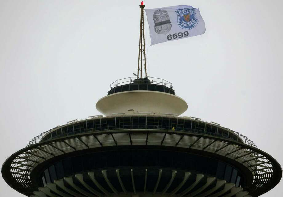 A flag flies atop Seattle's Space Needle on Nov. 5, 2009 honoring Officer Timothy Brenton who was killed on Halloween while he sat in his patrol car with an officer who was undergoing training. Photo: Joshua Trujillo / Seattlepi.com