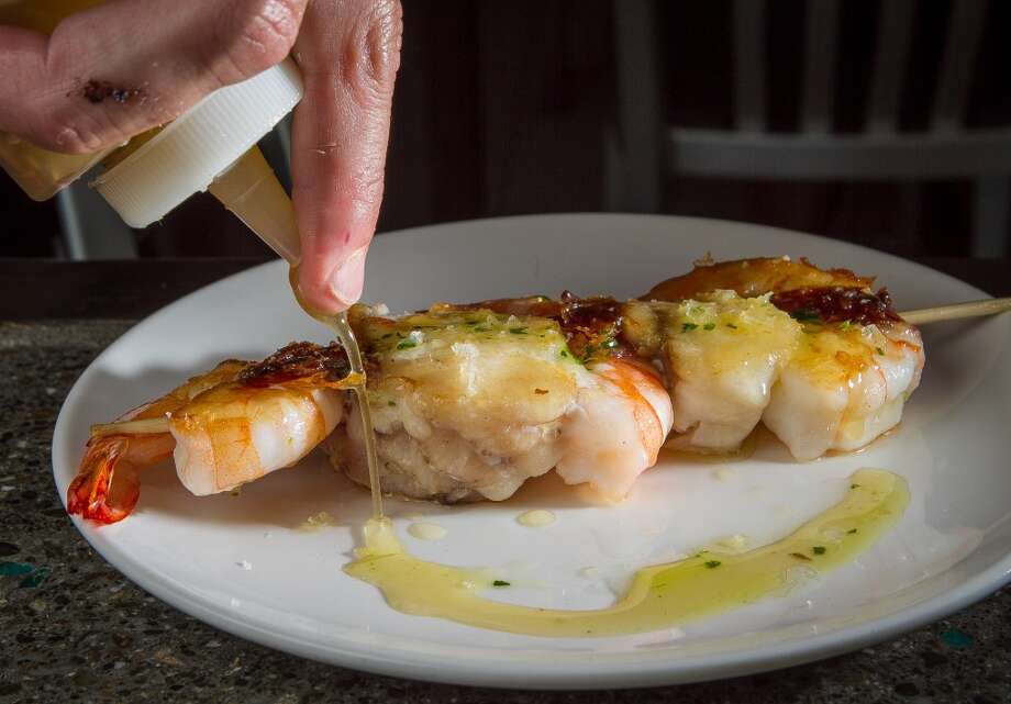 The skewer of Monkfish, Prawns and Jamon being sauced at Donostia.