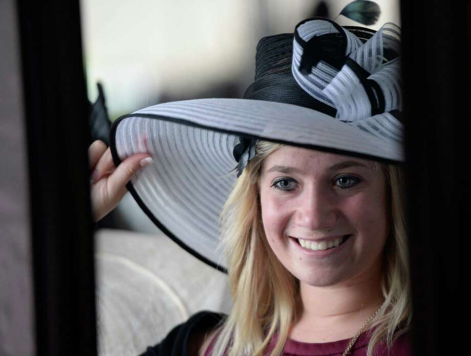 Sarah Kovachick adjusts a hat at the Hat sational booth at the American Cancer Society's annual fundraiser Dogs & Divas Fashion Show Thursday June 13, 2013 at the Saratoga National Golf Course in Saratoga Springs, N.Y.     (Skip Dickstein/Times Union) Photo: SKIP DICKSTEIN / 00022794A