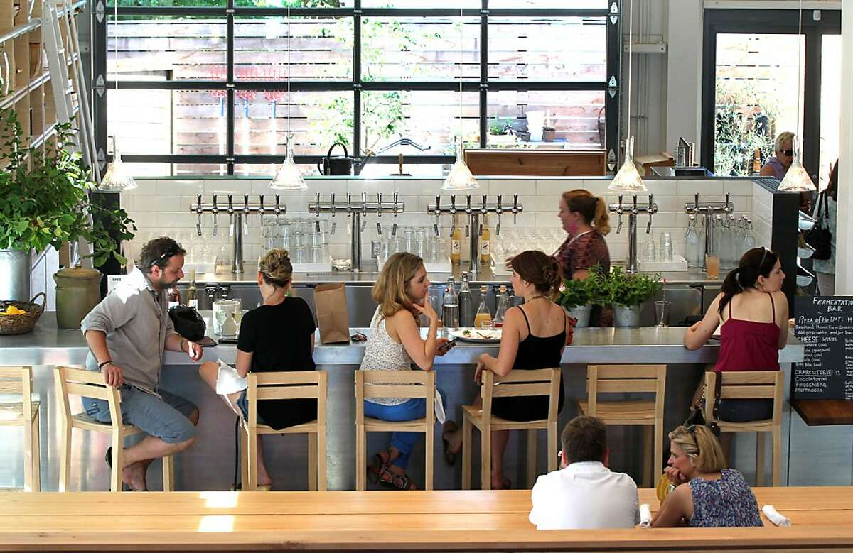 """Guest at the Shed relax at the fermentation bar. The Shed, a unique new food venue in Healdsburg recently opened calling itself a """"contemporary Grange, """" focusing on artisan food, and the gardening community. It includes a cafe, market, and cookware. They also offer classes and specialty dinners Saturday, June 8, 2013 in Healdsburg Calif."""