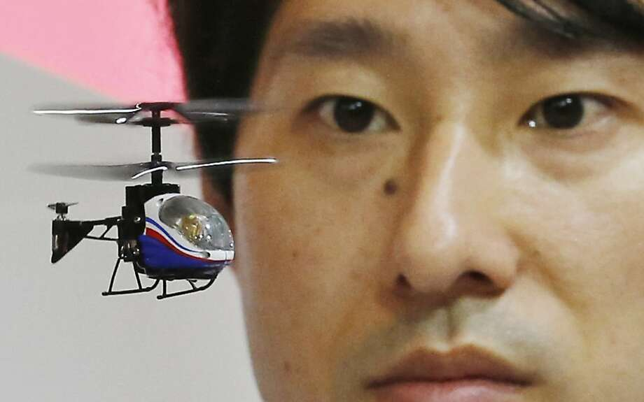 "A staff member of the Japanese toy and home appliances maker CCP Co. operates a ""Nano-Falcon,"" the world's smallest infrared remote-controlled helicopter, at the Tokyo Toy Show in Tokyo Thursday, June 13, 2013. The toy helicopter measures 8 centimeter (3.1 inches) in length while weighing 11 grams (0.39 ounces). It's now on sale at 4,704 yen ($50) on the domestic market. (AP Photo/Koji Sasahara) Photo: Koji Sasahara, Associated Press"