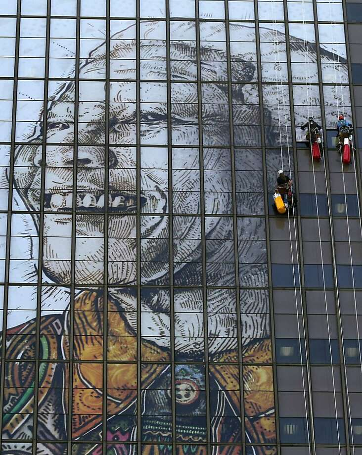 Wall of Mandela:Workers install a portrait of former president Nelson Mandela on the facade of a 