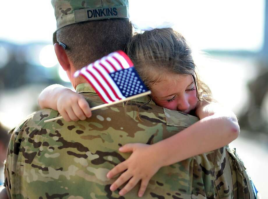 Welcome home, Dad! Olivia Chastain hugs her father, Army Staff Sgt. Jason Dinkins of 