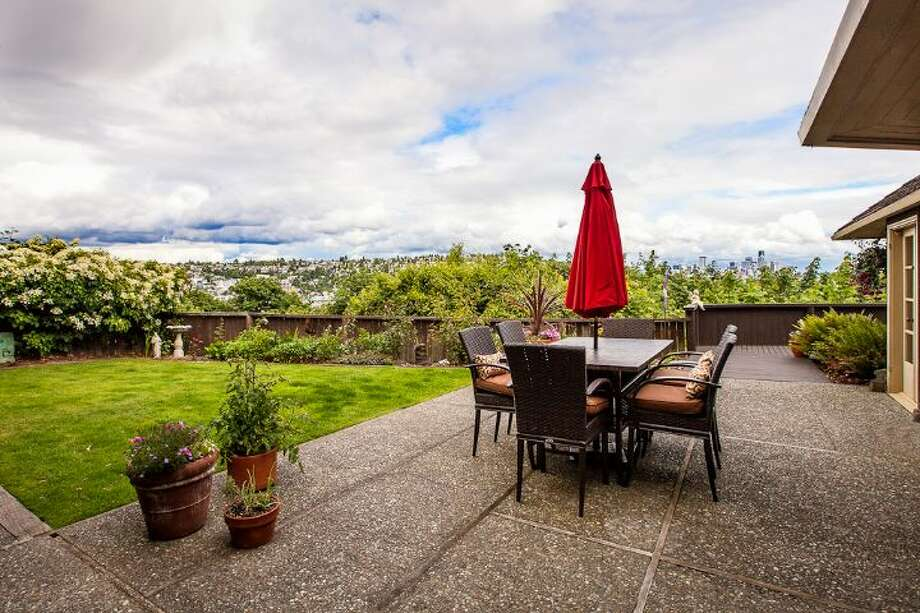 Patio of 1706 Magnolia Way W. The 4,890-square-foot house, built in 1900, has four bedrooms, 3.25 bathrooms, a two-story great room, a courtyard, a deck, and views of Elliott Bay, downtown Seattle and Mount Rainier on a 0.4-acre lot. It's listed for $1.45 million. Photo: Courtesy Scott And Molly Shutes, Windermere Real Estate
