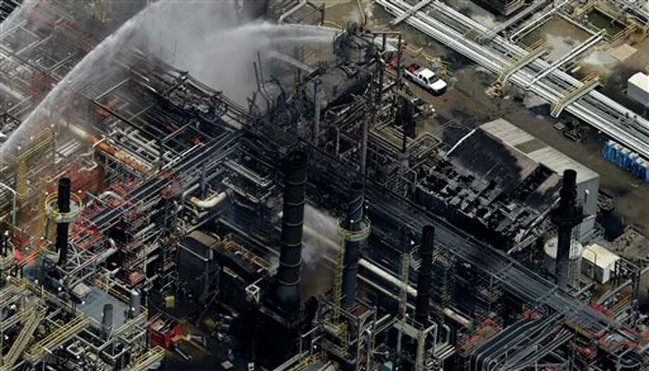 A chemical plant is hosed down after a fire in this aerial photo about twenty miles southeast of Baton Rouge, in Geismer, La., Thursday, June 13, 2013. The plant makes highly flammable gases that are basic building blocks in the petrochemical industry. Photo: Gerald Herbert, AP / AP