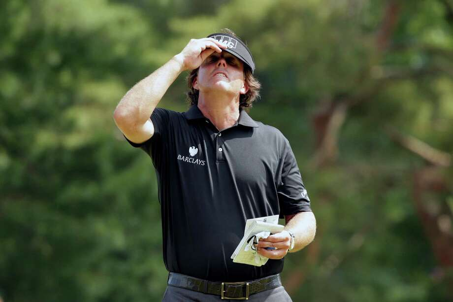 Phil Mickelson adjust his visor after putting on the 10th hole during the first round of the U.S. Open golf tournament at Merion Golf Club, Thursday, June 13, 2013, in Ardmore, Pa. (AP Photo/Charlie Riedel) Photo: Charlie Riedel, Associated Press / AP