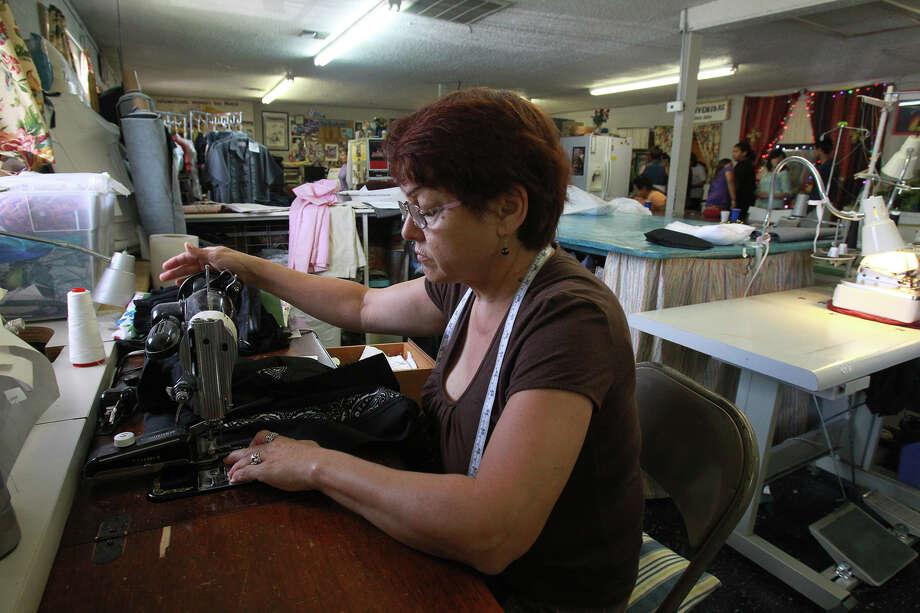 Leticia Garza joins seamstresses working on guayabera shirts with a San Antonio Spurs motif. Photo: John Davenport, San Antonio Express-News / ©San Antonio Express-News/Photo may be sold to the public