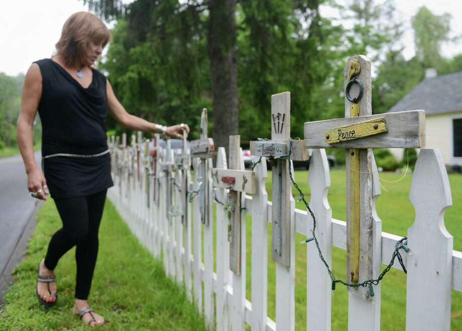 "Kim Bald, a paraeducator at Broadview Middle School in Danbury, shows her commemorative crosses for victims of the Sandy Hook Elementary School shooting outside of her Newtown, Conn. home on Thursday, June 13, 2013.  Bald and 25 of her colleagues wrote positive words on the crosses, starting with ""hope"" and ending with ""peace.""  The crosses use recycled or found material and Bald hopes to collect donations from the crosses which will benefit the Newtown carousel project. Photo: Tyler Sizemore / The News-Times"