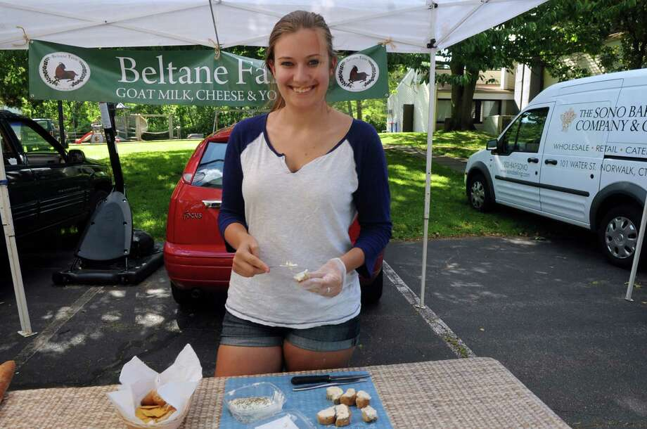 Mary Zawatski, of Beltane Farm, Lebanon, gives a sample of goat milk cheese at Old Greenwich Farmer's Market at the Presbyterian Church of Old Greenwich, Wednesday, June 13, 2013. The market is held every Wednesday at the church from 3 -6 p.m. Photo: Helen Neafsey / Greenwich Time