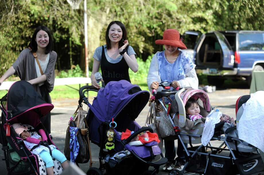 From left, Akiko with Nina, 24-months-old; Aynno with Oki, 3-month-old;  and Naoko with Rika and Dodoka, both 10-months-old, shopping at Old Greenwich Farmer's Market at the Presbyterian Church of Old Greenwich, Wednesday, June 13, 2013. The market is held every Wednesday at the church from 3 -6 p.m. Photo: Helen Neafsey / Greenwich Time