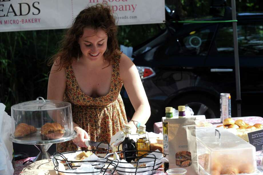 Kelsey Nichols, of Wave Hill Breads Bakery & Cafe Norwalk, shows different breads at Old Greenwich Farmer's Market at the Presbyterian Church of Old Greenwich, Wednesday, June 13, 2013. The market is held every Wednesday at the church from 3 -6 p.m. Photo: Helen Neafsey / Greenwich Time