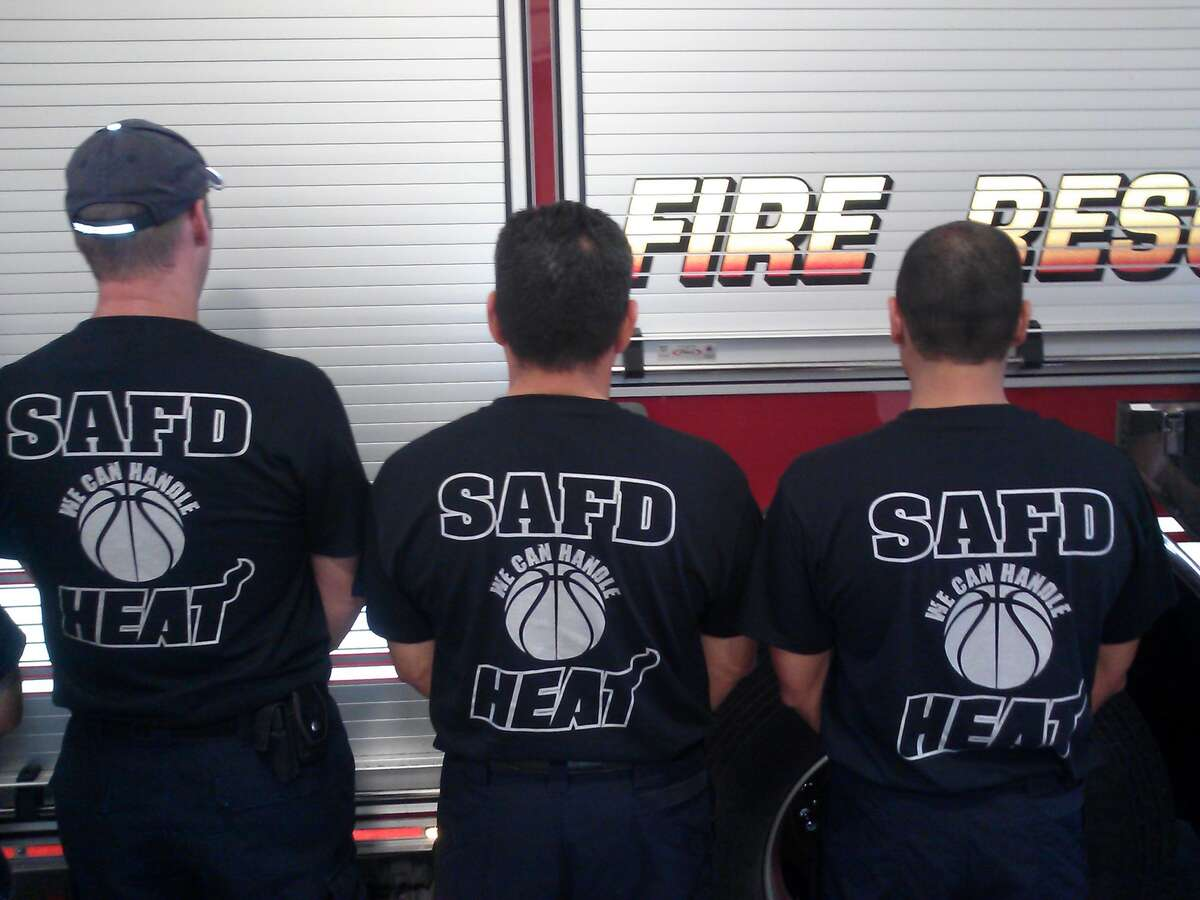 SAFD firefighters show off their new shirts supporting the Spurs bid for the 2013 Finals. Proceeds from shirt sales will go to the Houston firefighters who died or were injured in the May 31 five-alarm fire in Houston.