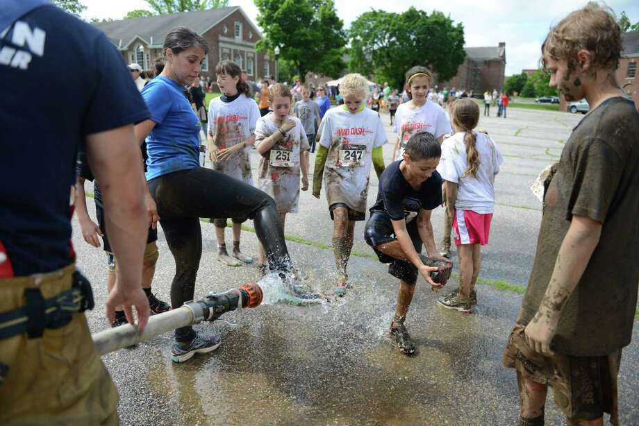 Robert Accomando, 9, of Sandy Hook, cleans mud off of himself after running in the 2013 Newtown Mad Dash at the Fairfield Hills campus in Newtown, Conn. on Saturday, June 8, 2013. Photo: Tyler Sizemore / The News-Times