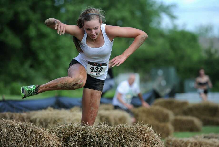 Lindsay Scott, of Southbury, jumps over a bail of straw to complete one of the nine course obstacles. Photo: Tyler Sizemore / The News-Times