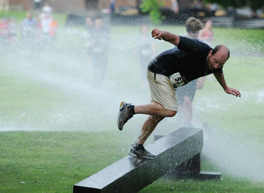 Craig Skenc, of Middlebury, tries to keep his balance while walking across the water cannon balance beam.  Firefighters stood on both sides of the beam, shooting water as race participants walked across. Photo: Tyler Sizemore / The News-Times
