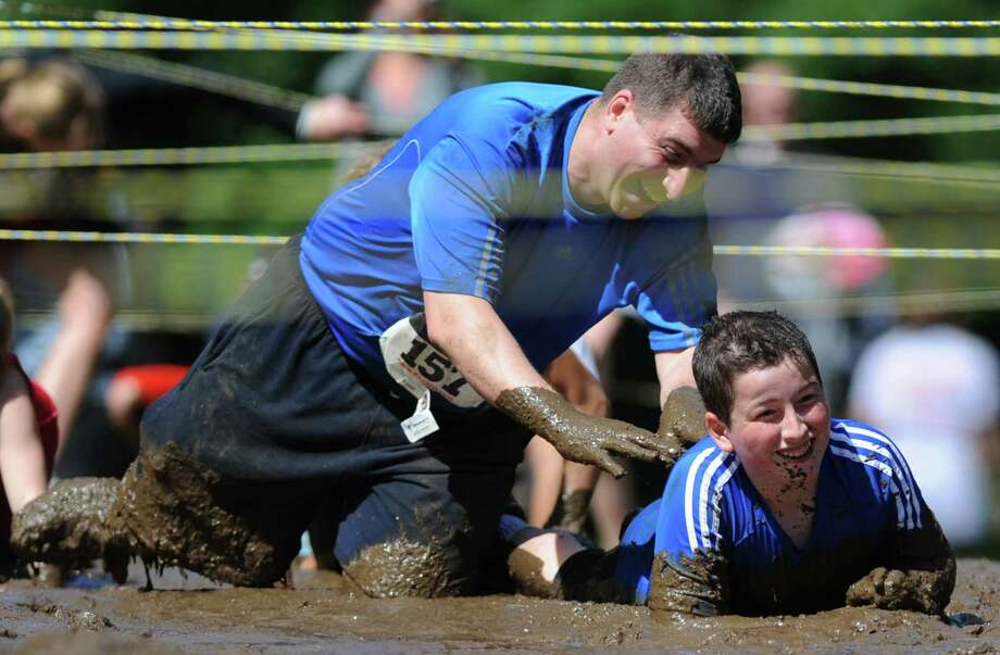Antonio Villanueva, of Brookfield, throws mud on his son, Brian Villanueva, 11, while going through the mud pit in the 2013 Newtown Mad Dash adventure race. Photo: Tyler Sizemore / The News-Times