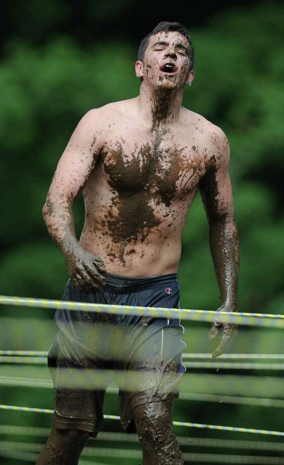 Kyle Morrissey, of Newtown, gets coated in mud while going through the mud pit. Photo: Tyler Sizemore / The News-Times