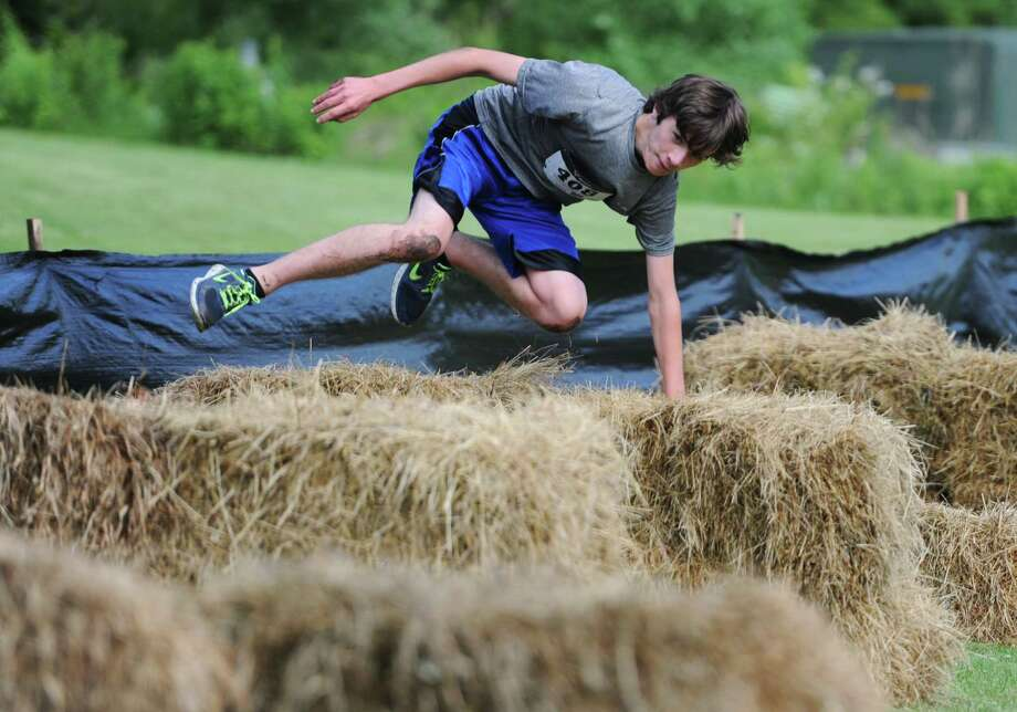 Cary DeYoung, of Newtown, jumps over bails of straw in the 2013 Newtown Mad Dash at the Fairfield Hills campus in Newtown, Conn. on Saturday, June 8, 2013.  The second annual adventure run featured nine obstacles, including a climbing wall, balance beam, tire run and a mud pit.  Over 400 runners participated between the two divisions with Newtown's Kevin Hoyt placing first in the advanced division. Photo: Tyler Sizemore / The News-Times