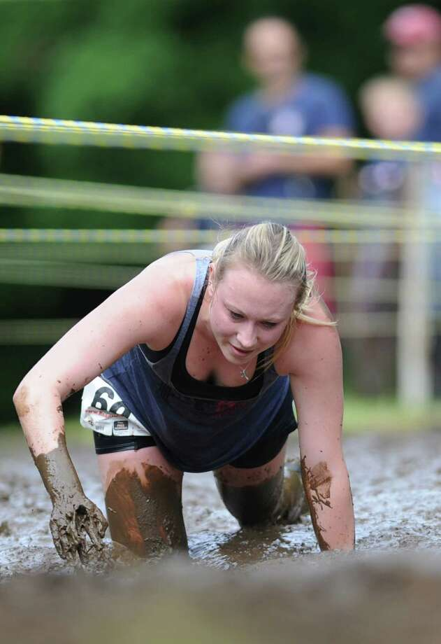 Kasey Sullivan, of Newtown, crawls through the mud pit in the 2013 Newtown Mad Dash at the Fairfield Hills campus in Newtown, Conn. on Saturday, June 8, 2013.  The second annual adventure run featured nine obstacles, including a climbing wall, balance beam, tire run and a mud pit.  Over 400 runners participated between the two divisions with Newtown's Kevin Hoyt placing first in the advanced division. Photo: Tyler Sizemore / The News-Times