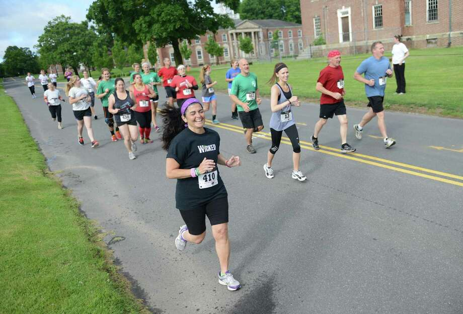 Christine DeVellis, of Newtown, runs with the pack in the 2013 Newtown Mad Dash at the Fairfield Hills campus in Newtown, Conn. on Saturday, June 8, 2013.  The second annual adventure run featured nine obstacles, including a climbing wall, balance beam, tire run and a mud pit.  Over 400 runners participated between the two divisions with Newtown's Kevin Hoyt placing first in the advanced division. Photo: Tyler Sizemore / The News-Times