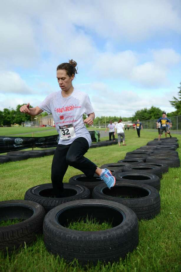 Melissa Singlak, of Newtown, runs through tires in the 2013 Newtown Mad Dash at the Fairfield Hills campus in Newtown, Conn. on Saturday, June 8, 2013.  The second annual adventure run featured nine obstacles, including a climbing wall, balance beam, tire run and a mud pit.  Over 400 runners participated between the two divisions with Newtown's Kevin Hoyt placing first in the advanced division. Photo: Tyler Sizemore / The News-Times