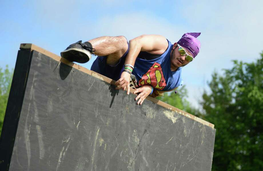 Joe DeVellis, of Newtown, climbs a wall during the 2013 Newtown Mad Dash at the Fairfield Hills campus in Newtown, Conn. on Saturday, June 8, 2013.  The second annual adventure run featured nine obstacles, including a climbing wall, balance beam, tire run and a mud pit.  Over 400 runners participated between the two divisions with Newtown's Kevin Hoyt placing first in the advanced division. Photo: Tyler Sizemore / The News-Times