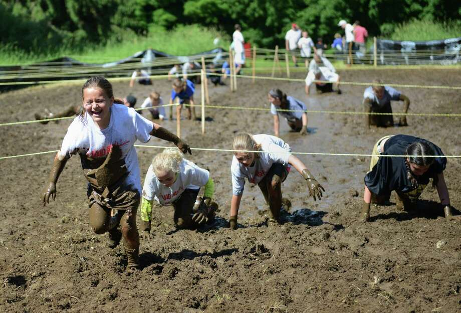 Runners trek through the mud pit in the 2013 Newtown Mad Dash at the Fairfield Hills campus in Newtown, Conn. on Saturday, June 8, 2013.  The second annual adventure run featured nine obstacles, including a climbing wall, balance beam, tire run and a mud pit.  Over 400 runners participated between the two divisions with Newtown's Kevin Hoyt placing first in the advanced division. Photo: Tyler Sizemore / The News-Times