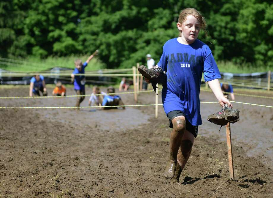 Jenna Reilly, of Newtown, loses her shoes while crawling through the mud pit in the 2013 Newtown Mad Dash at the Fairfield Hills campus in Newtown, Conn. on Saturday, June 8, 2013.  The second annual adventure run featured nine obstacles, including a climbing wall, balance beam, tire run and a mud pit.  Over 400 runners participated between the two divisions with Newtown's Kevin Hoyt placing first in the advanced division. Photo: Tyler Sizemore / The News-Times