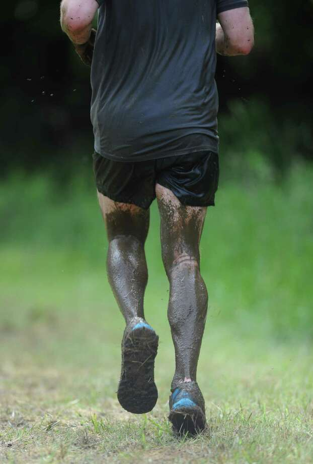 A runners exits the mud pit, covered in mud, during the 2013 Newtown Mad Dash at the Fairfield Hills campus in Newtown, Conn. on Saturday, June 8, 2013.  The second annual adventure run featured nine obstacles, including a climbing wall, balance beam, tire run and a mud pit.  Over 400 runners participated between the two divisions with Newtown's Kevin Hoyt placing first in the advanced division. Photo: Tyler Sizemore / The News-Times