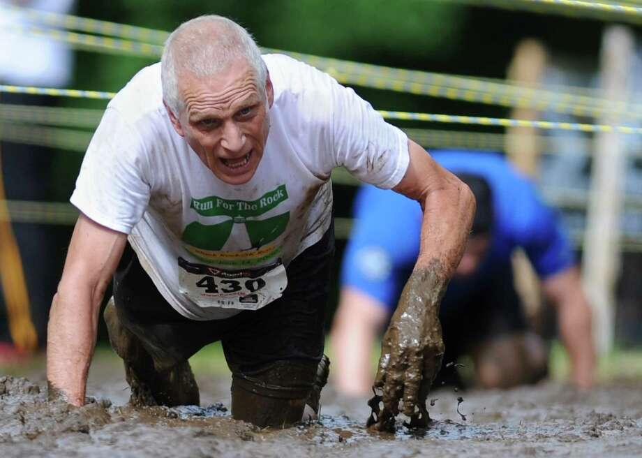 Bruce Goulart, of Newtown, crawls through the mud pit during the 2013 Newtown Mad Dash at the Fairfield Hills campus in Newtown, Conn. on Saturday, June 8, 2013.  The second annual adventure run featured nine obstacles, including a climbing wall, balance beam, tire run and a mud pit.  Over 400 runners participated between the two divisions with Newtown's Kevin Hoyt placing first in the advanced division. Photo: Tyler Sizemore / The News-Times