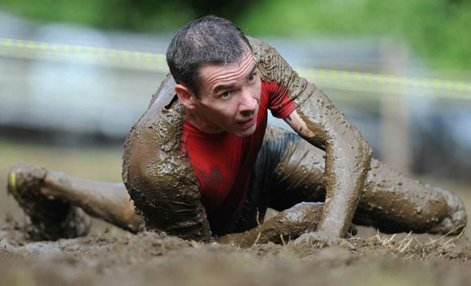 A runner goes through the mud pit in the 2013 Newtown Mad Dash at the Fairfield Hills campus in Newtown, Conn. on Saturday, June 8, 2013.  The second annual adventure run featured nine obstacles, including a climbing wall, balance beam, tire run and a mud pit.  Over 400 runners participated between the two divisions with Newtown's Kevin Hoyt placing first in the advanced division. Photo: Tyler Sizemore / The News-Times