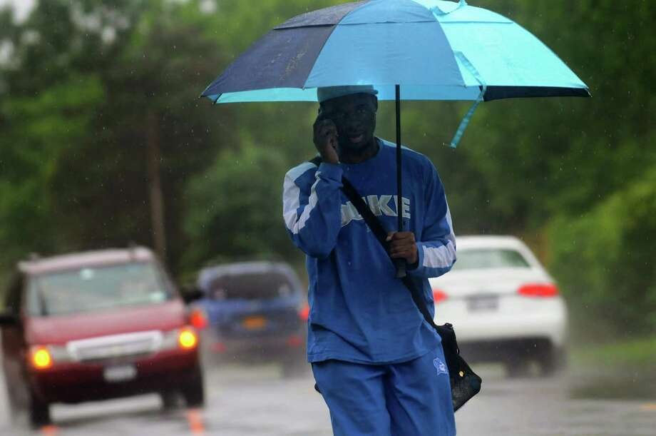 Keron Coffin, 20, of Albany takes shelter from the rain on Thursday, June 13, 2013, in Colonie, N.Y. (Cindy Schultz / Times Union) Photo: Cindy Schultz