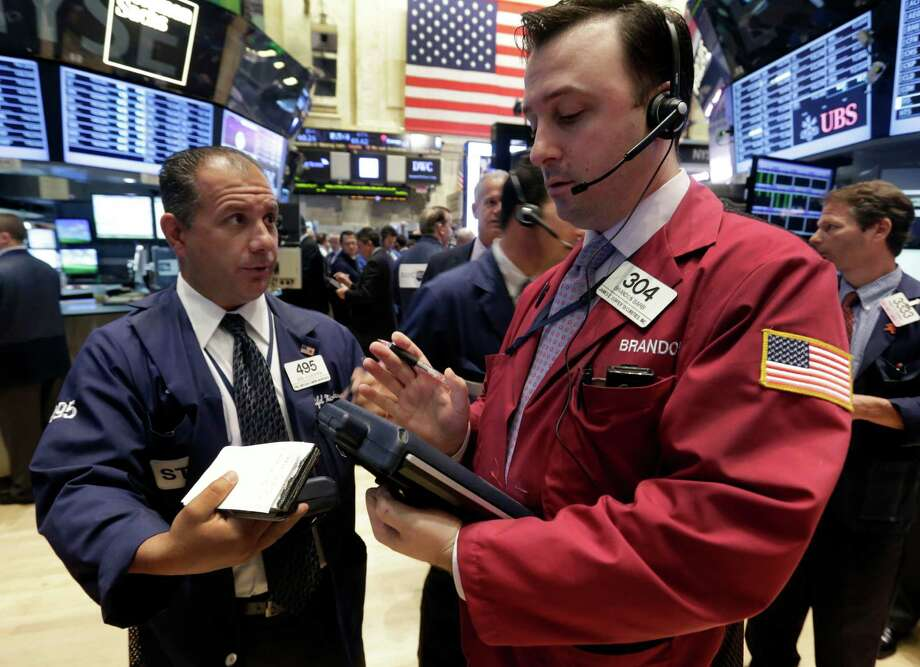 In this Monday, June 10, 2013 photo, traders Joel Lucchese, left, and Brandon Barb confer on the floor of the New York Stock Exchange. Global stock markets endured sharp losses Thursday June 13, 2013 as gyrations on the Tokyo market, the Asian region's biggest, continued _ fueled by worries about a surging yen and monetary policies in the U.S. (AP Photo/Richard Drew) Photo: Richard Drew