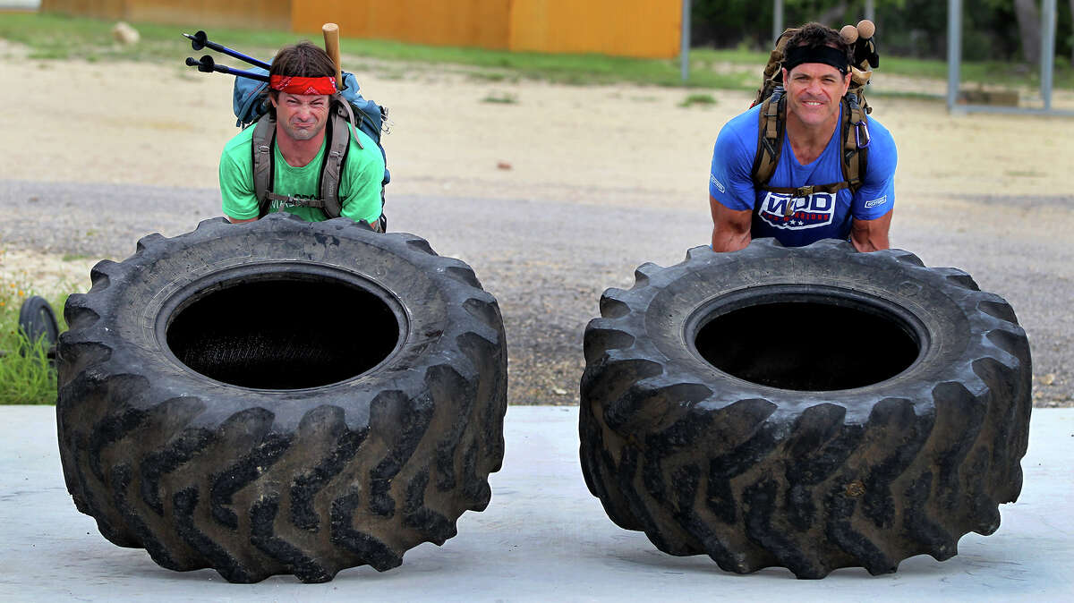 Marc Miller (left) and Brandon Bonser lift giant tractor tires Wednesday June 12, 2013 at Comal CrossFit while training for the Spartan Death Race in Vermont. The race is an adventure race with extreme physical challenges such as carrying large loads, climbing mountains, sitting in frigid water and felling trees.
