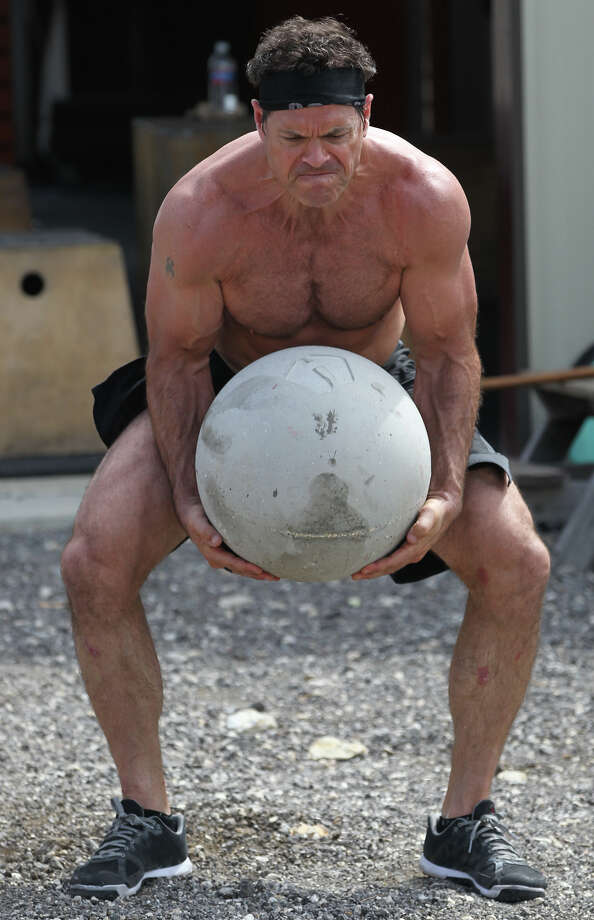 Brandon Bonser lifts a ball of concrete Wednesday June 12, 2013 at Comal CrossFit while training for the Spartan Death Race in Vermont. The race is an adventure race with extreme physical challenges such as carrying large loads, climbing mountains, sitting in frigid water and felling trees. Photo: JOHN DAVENPORT, SAN ANTONIO EXPRESS-NEWS / ©San Antonio Express-News/Photo may be sold to the public