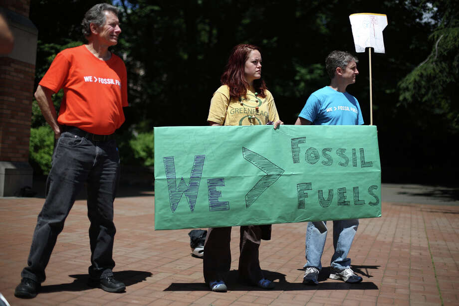 Participants hold a sign during a meeting of the University of Washington Board of Regents on Thursday, June 13, 2013. Students gathered during the meeting to ask the school to divest the university's investment portfolio of all stocks in big oil, big coal, and all companies involved in the fossil-fuel economy. Photo: JOSHUA TRUJILLO, SEATTLEPI.COM / SEATTLEPI.COM