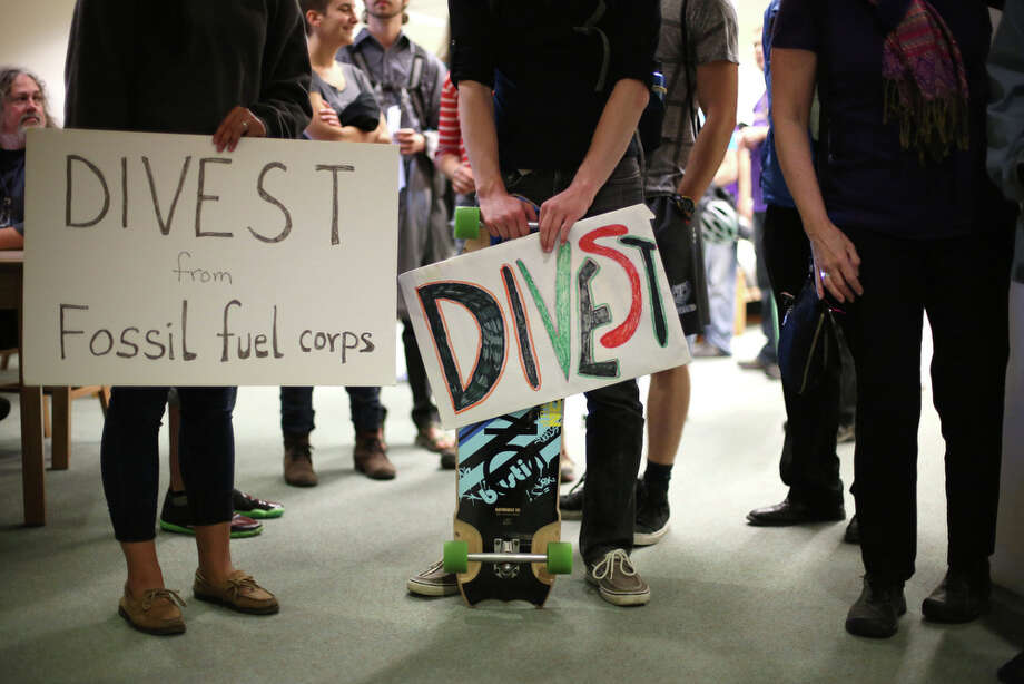 during a meeting of the University of Washington Board of Regents on Thursday, June 13, 2013. Students gathered during the meeting to ask the school to divest the university's investment portfolio of all stocks in big oil, big coal, and all companies involved in the fossil-fuel economy. Photo: JOSHUA TRUJILLO, SEATTLEPI.COM / SEATTLEPI.COM