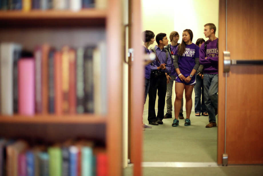 Students gather in a hallway during a meeting of the University of Washington Board of Regents on Thursday, June 13, 2013. Students gathered during the meeting to ask the school to divest the university's investment portfolio of all stocks in big oil, big coal, and all companies involved in the fossil-fuel economy. Photo: JOSHUA TRUJILLO, SEATTLEPI.COM / SEATTLEPI.COM