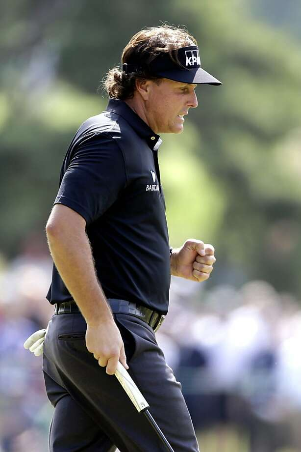Phil Mickelson, reacting to a putt on No. 9, was the leader among 78 golfers who finished the first round. Much of the field ran out of light and will complete the round Friday. Photo: Darron Cummings, Associated Press