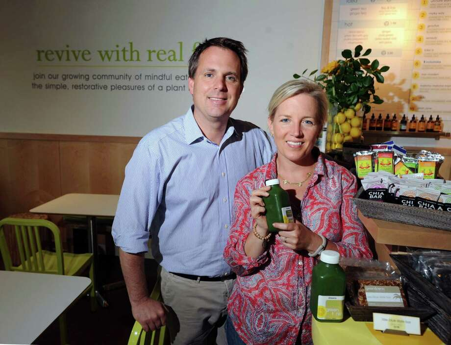 Husband and wife, Jeffrey and Cai Pandolfino, inside the restaurant they own, Green & Tonic, a quick-service eatery serving organic health food at 85 Railroad Ave., Greenwich, Thursday, June 13, 2013. Cai is holding a bottle of one of their establishment's best-selling jucies, the Green Monster, that consists of Romaine lettuce, celery, spinach, kale, cucumber, ginger, parsley, lemon, apple and Spirulina and sells for $7.50. Photo: Bob Luckey / Greenwich Time