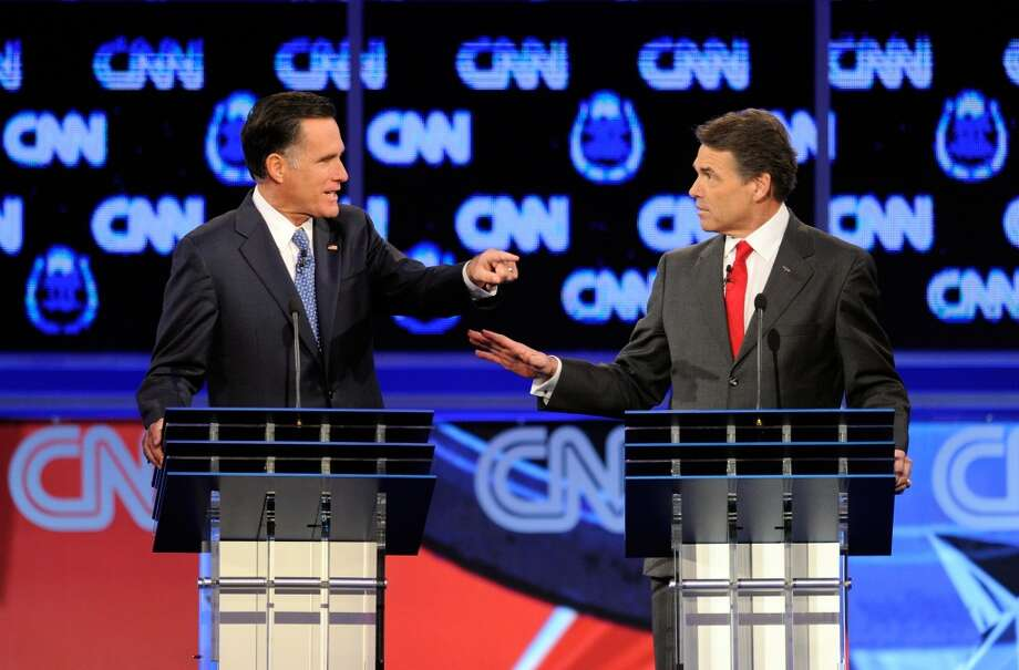 LAS VEGAS, NV - OCTOBER 18:  Former Massachusetts Gov. Mitt Romney (L) and Texas Gov. Rick Perry participate in the Republican presidential debate airing on CNN, October 18, 2011 in Las Vegas, Nevada. Seven GOP contenders are taking part in the debate, which is sponsored by the Western Republican Leadership Conference in Las Vegas and held in the Venetian Hotel's Sands Expo and Convention Center.  (Photo by Ethan Miller/Getty Images) Photo: Ethan Miller, Getty