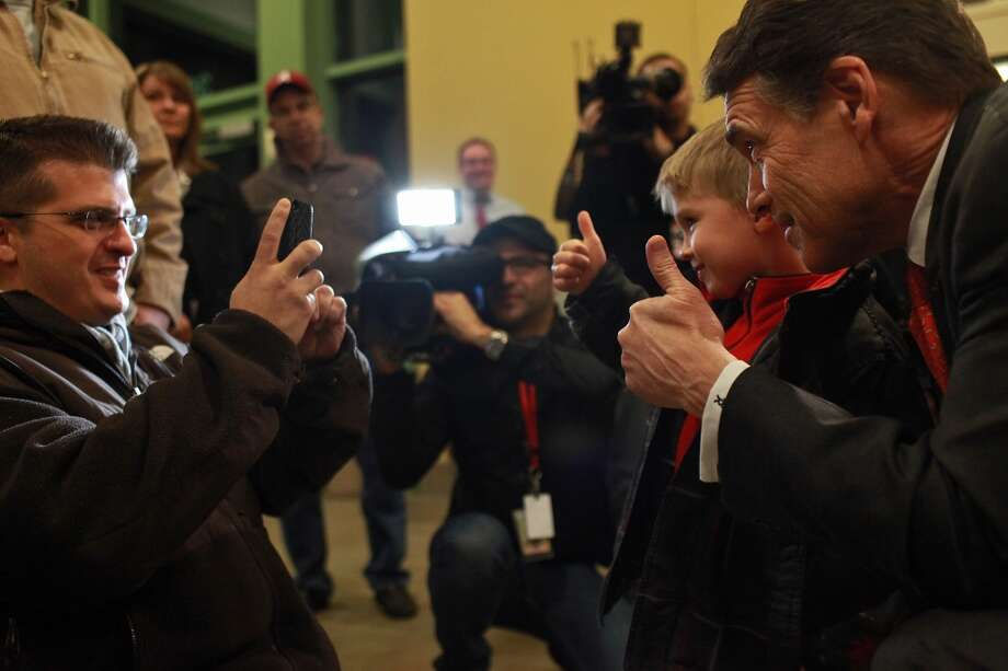 metro - Republican presidential candidate Governor Rick Perry poses with Griffin Mann, 4, while his father, Robert Mann, of Urbandale, takes their picture as Mann waits in line to sign in for the caucus meeting at Point of Grace Church in Waukee, IA, representing Walnut Grimes Urbandale Precinct and Waukee 3 Precinct, onTuesday, Jan. 3, 2012. LISA KRANTZ/lkrantz@express-news.net Photo: LISA KRANTZ, SAN ANTONIO EXPRESS-NEWS