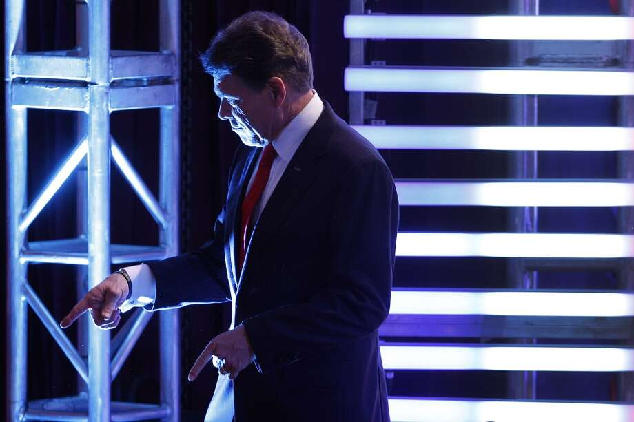 Texas Gov. Rick Perry points to a member of the audience during a break in the Republican presidential candidate debate at Saint Anselm College in Manchester, N.H., Saturday, Jan. 7, 2012. (AP Photo/Elise Amendola) Photo: Elise Amendola, Associated Press
