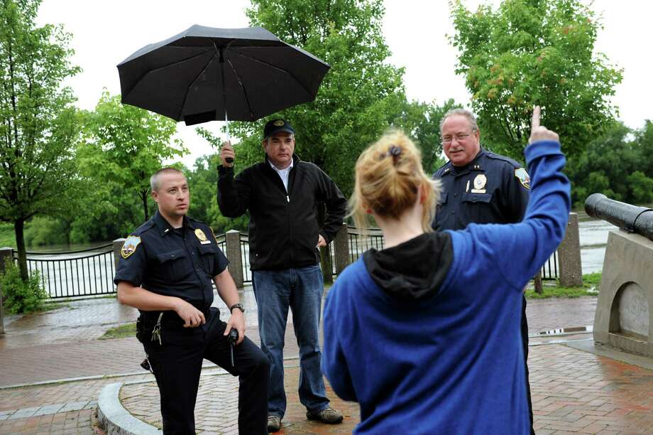 During a break in the rain, resident Debbi Taylor, foreground, talks with Lt. Brian Bienduga, left, Mayor Gary McCarthy, center, and Asst. Chief Jack Falvo about possible flooding in the Stockade neighborhood on Thursday, June 13, 2013, at Riverside Park in Schenectady, N.Y. Taylor said she had just replaced her furniture from the flood of 2011. Schenectady police were warning residents about the rising Mohawk River. (Cindy Schultz / Times Union) Photo: Cindy Schultz