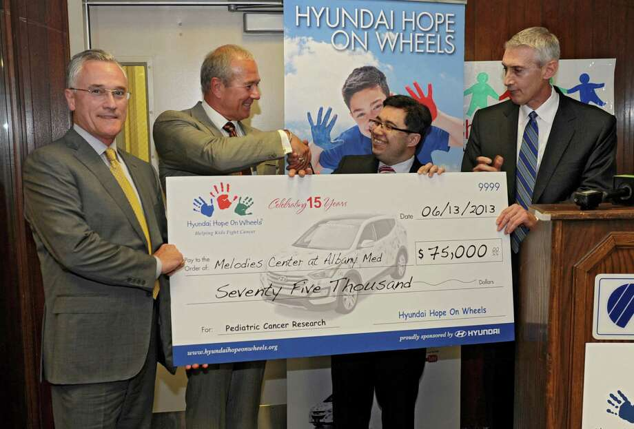 Dr. Alexander Gozman, second from right, receives a check for $75,000 for his work, which includes reducing stress in parents of children with cancer at Albany Medical Center on Thursday, June 13, 2013 in Albany, N.Y. The grant came from the Hyundai Hope On Wheels program and was presented by (L to R) Sean Garvey and Marc Garvey of Garvey Hyundai and Dave O'Brien, Hyundai regional sales manager. (Lori Van Buren / Times Union) Photo: Lori Van Buren / 00022792A